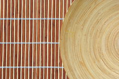 High definition round wooden dish on bamboo. Background Stock Photo