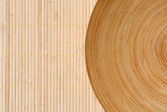 High definition round wooden dish on bamboo. Background Stock Photography
