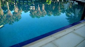 High definition video - Sunbeds and umbrellas around the pool at the hotel. Reflection of trees in water stock video