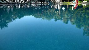 High definition video - Sunbeds and umbrellas around the pool at the hotel. Reflection of trees in water stock footage