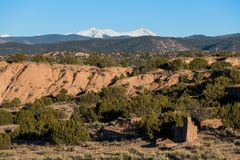 Desert red rock landscape contrasted with trees and snow-capped mountain peaks near Santa Fe, New Mexico. High desert red rock landscape contrasted with junipers royalty free stock photography