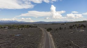 High Desert Before a Thunderstorm. High Desert with Cumulus Clouds. A road, surrounded by bucket brush, leads you to mountains with snow stock image