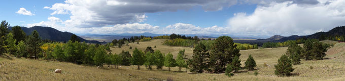 High Desert Valley Panorama. A Beautiful day in the Valley of the high desert of the Sangre De Cristo Mountains in Southern Colorado. Puffy clouds casting stock photo