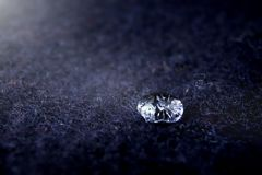 High detail close-up of sparkling drop of water on dark blue boild wool - bright light mood with deep shadows. Foreground and background blanked out blurry royalty free stock photos