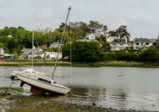 High and Dry. Small yacht left high and dry by the receding tide Royalty Free Stock Images