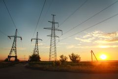 High electricity power line towers at dramatic sunset. Background Royalty Free Stock Photos