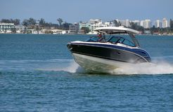 High-end Motorboat Speeding on the Intra-coastal Waterway. A blue motor boat with white trim and a white fiber glass canopy speeding on the Florida intra-Coastal royalty free stock photography
