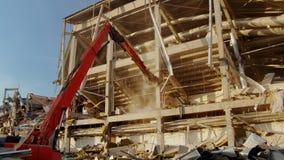 High excavator crusher destroys column of old hockey stadium