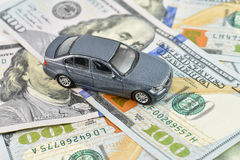 High expenses transportation car leasing concept. Toy car on dollar money, concept image for buying, renting, fuel or service and repair costs Royalty Free Stock Photography
