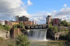 High Falls and city skyline Rochester, New York. View of the waterfall, riverbanks and city from the Pont De Rennes pedestrian bridge royalty free stock image