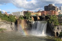 High Falls, rainbow and city skyline Rochester, New York. Sunshine through storm clouds creating a rainbow on the Genesee river Stock Photos