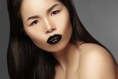 High Fashion Beauty Asian Model with bright Lip Gloss Make-up. Black Lips with gloss lipstick makeup. Long dark hair. Horisontal photo Royalty Free Stock Image