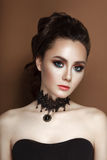 High Fashion Beauty Model Girl with collected brunette hair black corset and lace necklace. High Fashion Beauty Model Girl with Black Make up collected brunette Royalty Free Stock Images