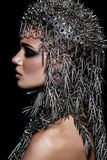 High fashion beauty model with metallic headwear and dark makeup and blue eyes on black background Royalty Free Stock Photography