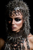 High fashion beauty model with metallic headwear and dark makeup and blue eyes on black background Stock Photography