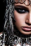 High fashion beauty model with metallic headwear and dark makeup and blue eyes on black background.  Royalty Free Stock Photography
