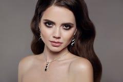 High Fashion brunette model woman in diamond jewellery set isol. High Fashion brunette model woman in diamond jewellery set on gray background. Beauty female royalty free stock image