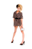 High Fashion Doll. Young blonde woman wearing a high fashion mini dress with big teased hair, a small clutch and a feather hair piece isolated over white Stock Photo