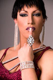 High Fashion Drag queen. Close up of an elegant Drag queen wearing a dark red velvet dress, and lots of jewelry, holding one finger up to her lips stock photography