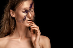 High fashion look, closeup beauty portrait of woman with bright makeup with gold skin with gold lips and purple stripe across face Stock Images