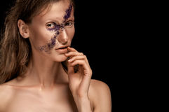High fashion look, closeup beauty portrait of woman with bright makeup with gold skin with gold lips and purple stripe across face Royalty Free Stock Photo