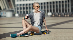 High fashion look. glamour joyful beautiful young blond girl in summer bright casual hipster clothes sitting on a little Royalty Free Stock Photography