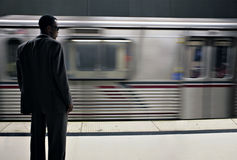 High Fashion Male Waiting for the Subway Train to. African American Businessman Waiting for the Subway Train. Intentional Blur, Image is Shot in High ISO Stock Photo
