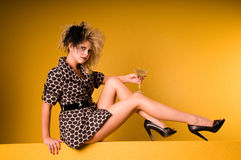 High Fashion Martini. Young blonde woman wearing a high fashion mini dress with big teased hair, a small clutch and a feather hair piece sitting on a yellow wall Stock Photography