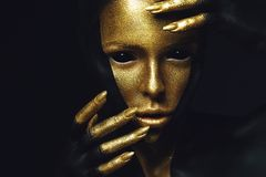 High fashion model with black and gold leather, golden fingers. Isolated on black background Beauty female face, creative make-up royalty free stock image