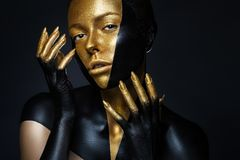 High fashion model with black and gold leather, golden fingers. Isolated on black background Beauty female face, creative make-up stock photography