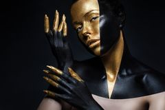 High fashion model with black and gold leather, golden fingers. Isolated on black background. Beauty female face, creative make-up stock images