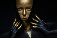 High fashion model with black and gold leather, golden fingers. Isolated on black background Beauty female face,. Creative make-up stock photo