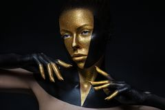 High fashion model with black and gold leather, golden fingers. Isolated on black background Beauty female face, creative make-up. High fashion model with black royalty free stock photo