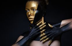 High fashion model with black and gold leather, golden fingers. Isolated on black background Beauty female face, creative make-up. High fashion model with black stock images