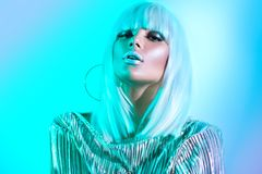 High fashion model girl in colorful bright neon lights posing in studio. Portrait of beautiful woman in white wig. And silver trendy glowing makeup royalty free stock photo