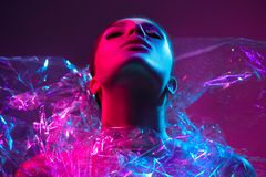 High Fashion model girl in colorful bright neon lights posing in studio through transparent film. Portrait of beautiful sexy woman