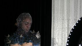 High-fashion. Model in the image of an alien girl in a black mask in sparkling rhinestones, sparkles, metal butterflies. On a black and silver background posing stock video