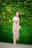 High fashion model with long tulle dress and ponytail standing u. P and looking to the camera, near a green leaves wall, in the park. High fashion pose stock photo