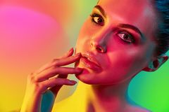 High Fashion model woman in colorful bright lights posing in studio. Portrait of beautiful girl with trendy make-up and manicure. Art design, colorful make up royalty free stock image