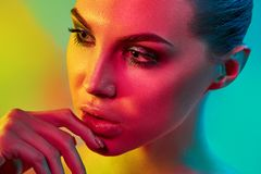 High Fashion model woman in colorful bright lights posing in studio. Portrait of beautiful girl with trendy make-up and manicure. Art design, colorful make up stock images