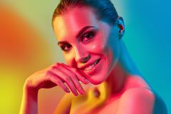 High Fashion model woman in colorful bright lights posing in studio. Portrait of beautiful girl with trendy make-up and manicure. Art design, colorful make up stock photography