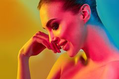 High Fashion model woman in colorful bright lights posing in studio. Portrait of beautiful girl with trendy make-up and manicure. Art design, colorful make up stock photos