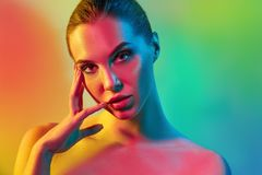 High Fashion model woman in colorful bright lights posing in studio. Portrait of beautiful girl with trendy make-up and manicure. Art design, colorful make up royalty free stock images