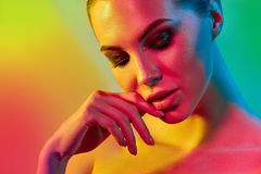 High Fashion model woman in colorful bright lights posing in studio. Portrait of beautiful girl with trendy make-up and manicure. Art design, colorful make up royalty free stock photography