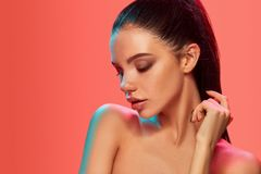 High Fashion model woman in colorful bright lights posing in studio. Portrait of beautiful girl with trendy make-up and manicure. Art design, colorful make up stock image
