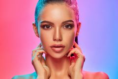 High Fashion model woman in colorful bright lights posing in studio. Portrait of beautiful girl with trendy make-up and manicure. Art design, colorful make up stock photo