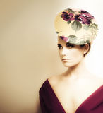 High Fashion Portrait. Artistic toned portrait of a woman in high fashion wearing a plunging neckline and floral pillbox hat Stock Photography