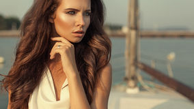 High fashion portrait of beautiful elegnt woman with silver ring. On her finger and sea with yacht on the background. Long wavy hair and profession make up Stock Image