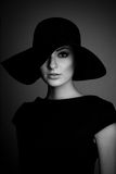 High fashion portrait of elegant woman in black and white hat an. D dress. Studio shot Stock Images