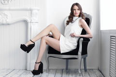High fashion shot of young beautiful woman in white short dress. Fashion shot of young beautiful woman in white short dress sitting in antique armchair Royalty Free Stock Images